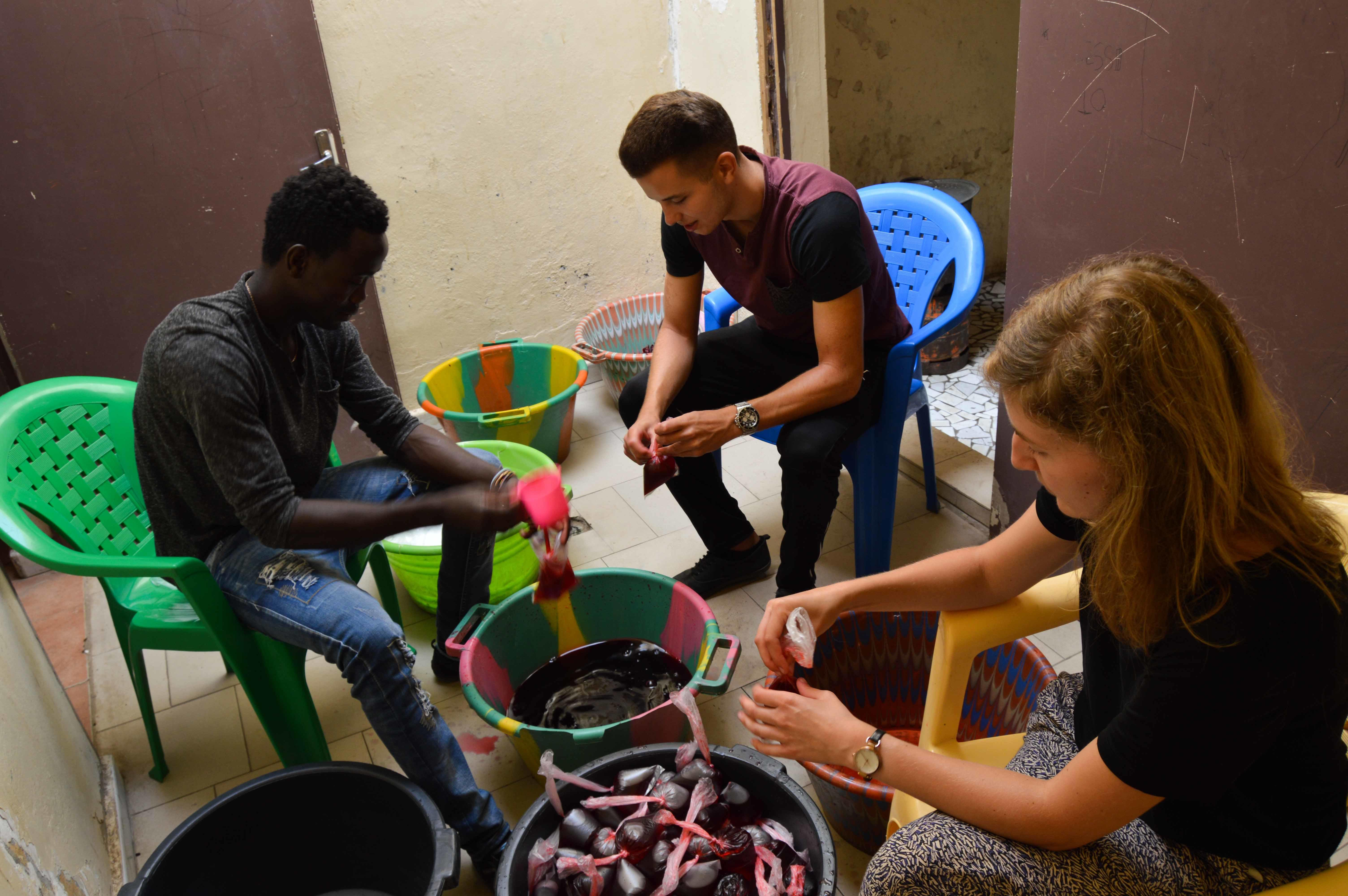 A group prepares juices for talibés while they volunteer with children in Senegal.